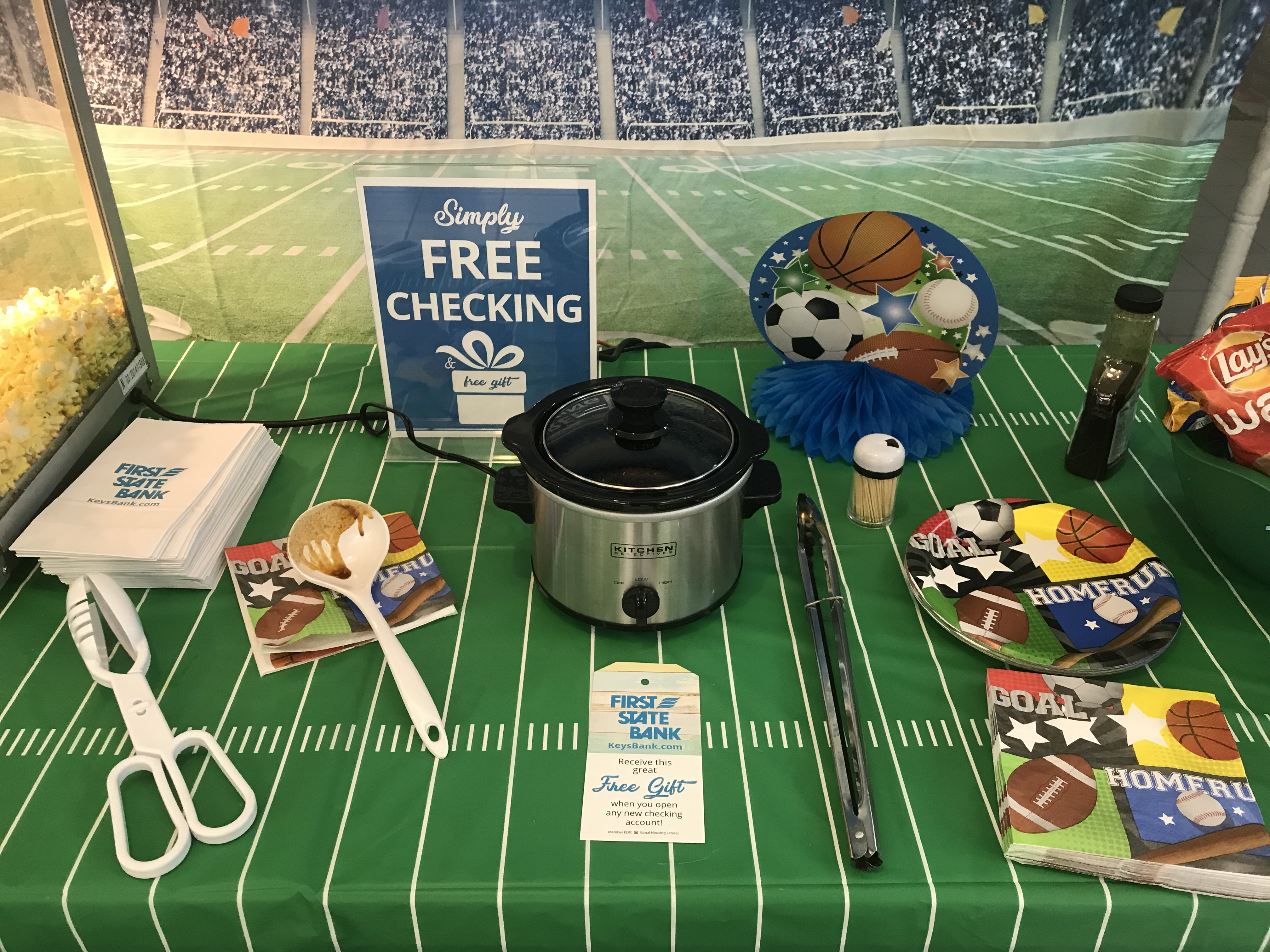 Table in lobby decorated with football team and slow cooker we are giving away with a Free Checking Account
